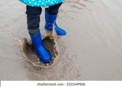 the child is dressed in rubber boots strongly stomps on a puddle. drops of dirty water spray everywhere.