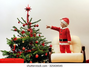 Child dressed in Santa Claus near the Christmas tree