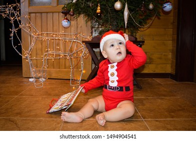 A child dressed as Santa Claus is sitting under a Christmas tree and looks admiringly into the right corner. Christmas concept