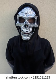 Child dressed as a skeleton with a golden silver head and a loose black hoodie for Halloween