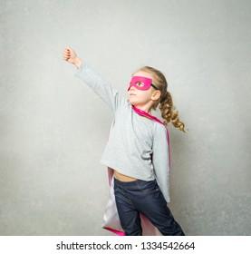 Child dressed as superhero showing her determination