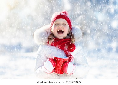 Child drinking hot chocolate with marshmallows in snowy winter park. Kid with cup of warm cocoa drink on Christmas vacation. Little girl playing in snow on Xmas eve. Family outdoor winter fun.