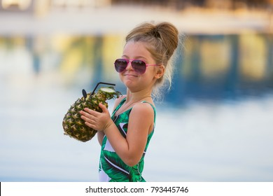 Child drinking juice in swimming pool bar. Summer family vacation with kids. Little girl holding fresh pineapple cocktail in swim up beach cafe. Kid with tropical fruit lemonade in luxury resort.