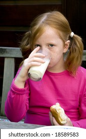 child is drinking milk and eating bread
