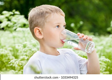 Child drinking pure water in nature in the park