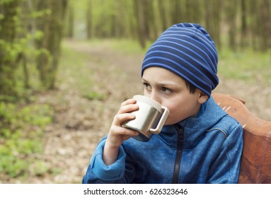 Child drinking tea from a flask cup while sitting on a bench in nature park.