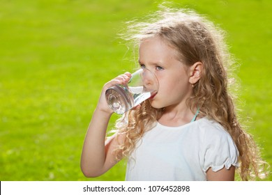Child drinking water. Girl outdoors