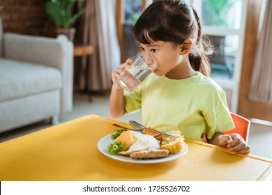 child drinking while having healthy breakfast at home in the morning