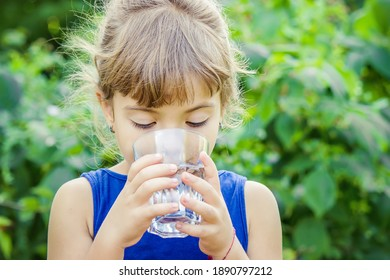 The child drinks clean water in summer. Selective focus. People.