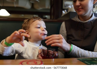 The child drinks juice in the restaurant