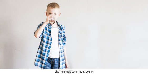 child drinks pure water from transparent glass