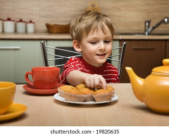 Child drinks tea with cakes