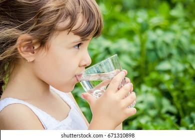 Child drinks water. - Shutterstock ID 671310898
