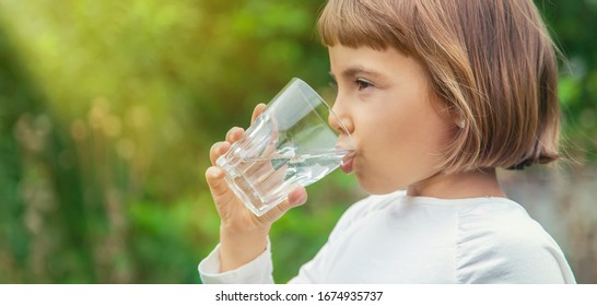 child drinks water from a glass. Selective focus.