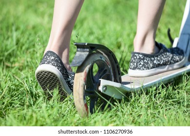 Child drives push stand-up scooter on green grass, close up rear view