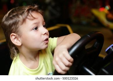 Child driving a car simulator at an amusement park