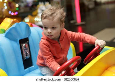 Child driving toy car in amusement park