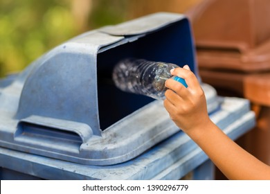 Child drop the empty plastic bottle into the blue bin in the park, trash sorting by leave the reuseable garbage in the recycle bin