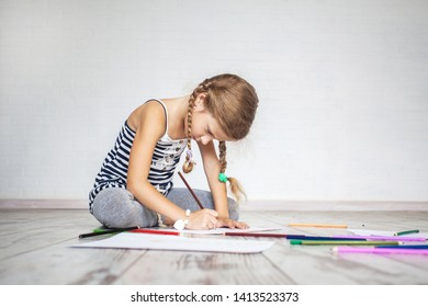 Child drowing at home. Girl playing