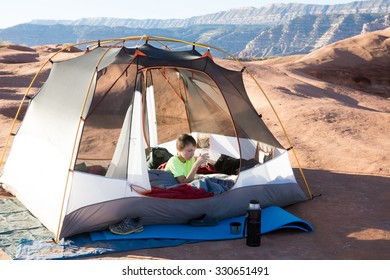 A child in the early morning in a tent on a stone plateau. Grand Staircase-Escalante National Monument, Utah