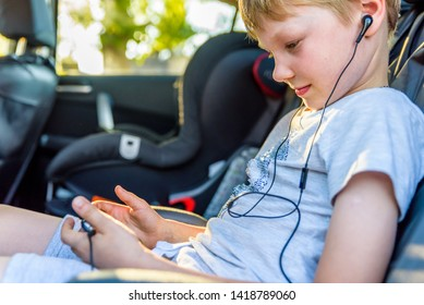 child with earphones inside car watching movie or listening music on his smartphone