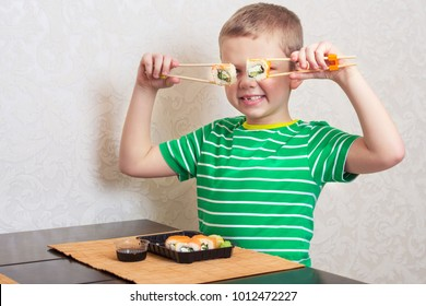 Child eat sushi rolls at home.