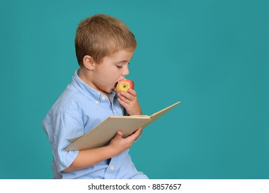 Child eating an apple and reading a book