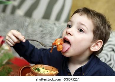 Child eating baked vegetables in a cafe