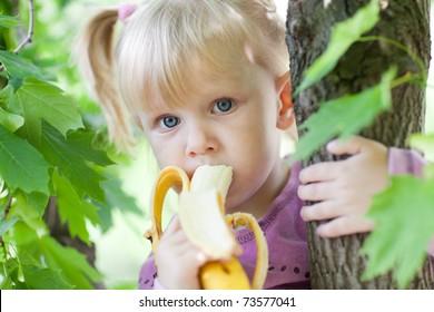 child eating banana on the tree