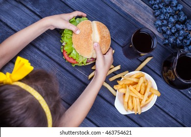 child eating a Burger at the wooden table. the view from the top