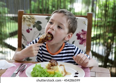 Child eating chicken leg in a cafe