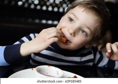 Child eating chicken nugget in a restaurant