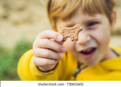 Child Eating Cookie On The Nature Background.