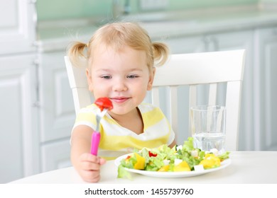 Child eating healthy food home.Kids nutrition,vegetables salad.Small girl having lunch.