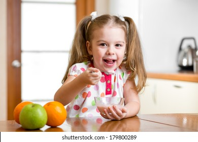 child eating healthy food in kitchen