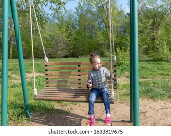 Child eating ice cream in a black waffle cone sitting on a swing