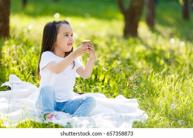 Child eating ice cream. Little girl on the grass with ice creamChildren eat icecream. Little girl with vanilla ice cone.
