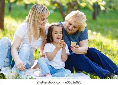 Child eating icecream together with her grandmother outdoor in nature Grandmother licking icecream from nose of her grandchild outdoor in nature