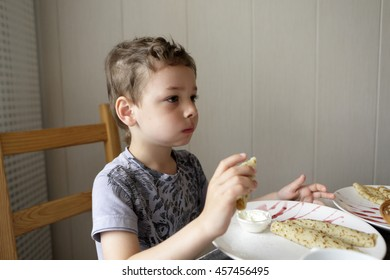 Child eating pancake in cafe in the morning