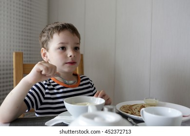Child eating porridge at hotel in the morning