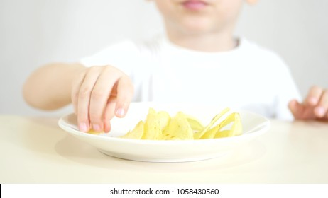 The child is eating potato chips. The focus of the camera is aimed at the plate with chips.