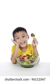 Child eating salad, shot in studio isolated on white background