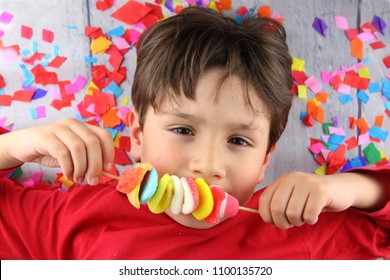 child eating skewer of colorful jelly beans in a floor with confetti
