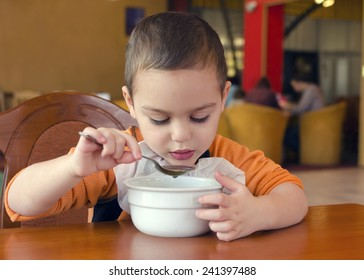 Child eating soup from a bowl in a restaurant