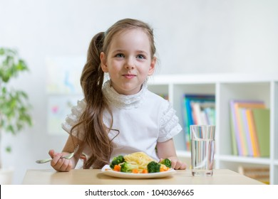 Child eating spaghetti with vegetables in daycare