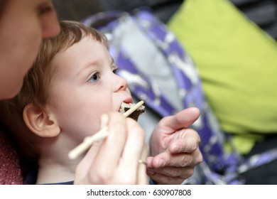 Child eating sushi from his mother hand