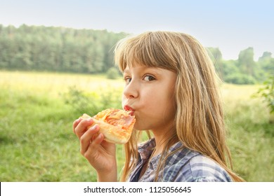 child eating a tasty pizza on the nature of the grass in the park