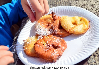 Child eating traditional apple fritters during autumn festival in Aosta Valley (Apple fest, Antey Saint André, Italy). Close up of hands, cutlery, white paper dish, artisanal fritters. Holyday food.
