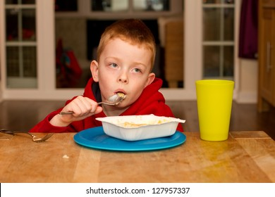 child eating an unhealthy processed dinner in front of the TV