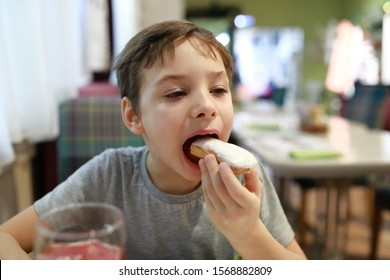 Child eating vanilla eclair in a restaurant